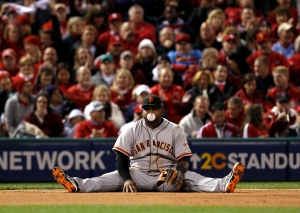 Image: San Francisco Giants third baseman Sandoval sits on the ground after making a diving stop but was late on the throw to get St. Louis Cardinals Craig at first in the seventh inning during Game 4 of their MLB NLCS playoff baseball series in St. Louis